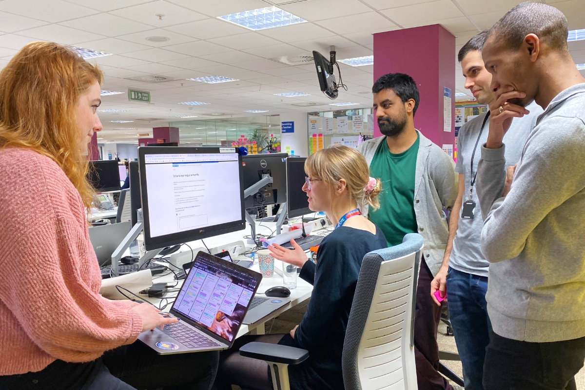 A group of colleagues gathered around a desktop in discussion