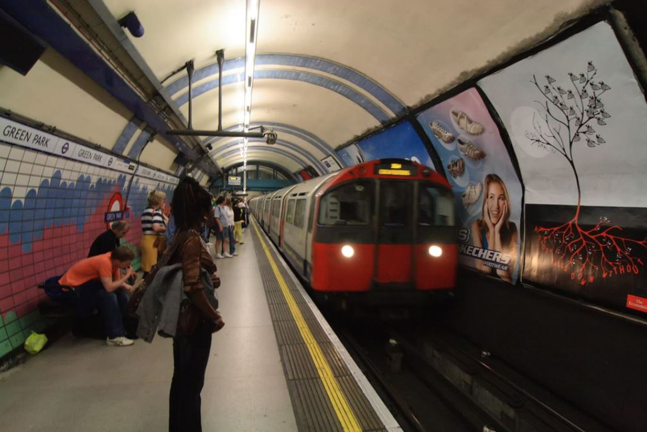 Woman standing on Green Park tube station platform as a tube passes by
