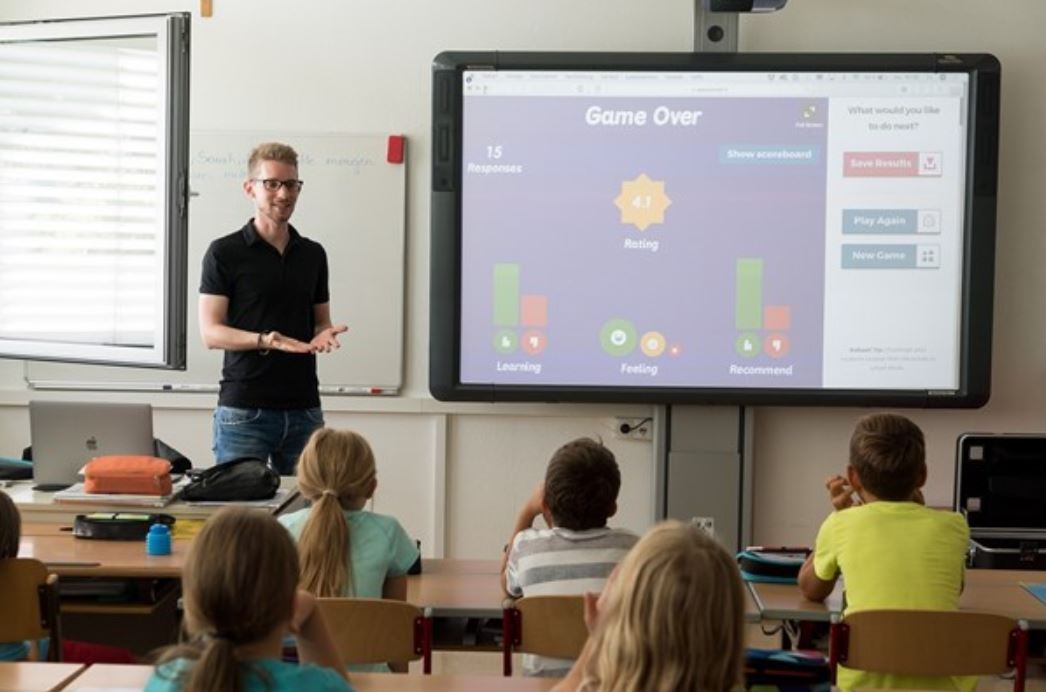 Male teacher with a classroom full of students looking at an interactive whiteboard