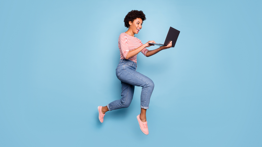 woman jumping holding laptop
