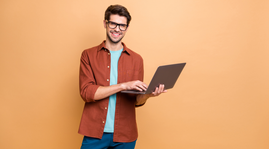 Man smiling using laptop on bright background